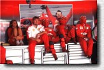 Ferrari pit crew in front of a poster of Michael