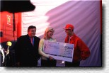 Michael Schumacher gives a cheque about DM 500,000.00 to Ute Ohoven, ambassador of the UNESCO. On the left Dr. Helmut Thoma, boss of the TV station RTL